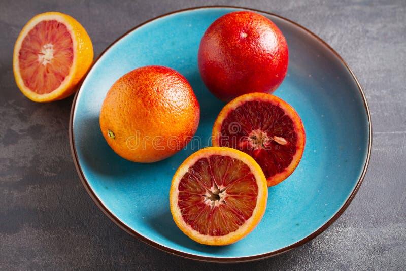 Sangue ou laranjas vermelhas na bacia azul no fundo cinzento Citrinas maduras frescas fotografia de stock royalty free