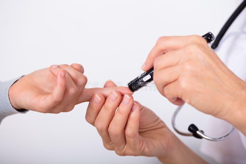 Sangue Sugar Level With Glucometer do doutor Measuring Patient imagens de stock