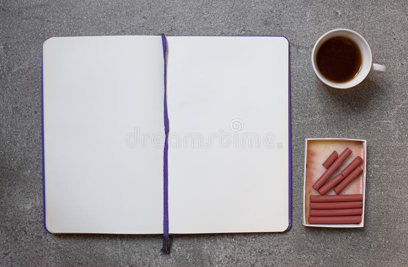 Sanguine for sketching on gray background with cup of coffee royalty free stock image