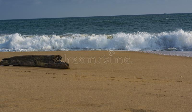 Solitary Log on the beach facing Waves - Sanguthurai. Sanguthurai is a small village in Kanyakumari district, Tamil Nadu, India, near Nagercoil. Sanguthurai stock photo