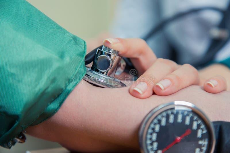 Sanità, concetto della medicina dell'ospedale - medico e pressione sanguigna di misurazione del paziente immagini stock libere da diritti