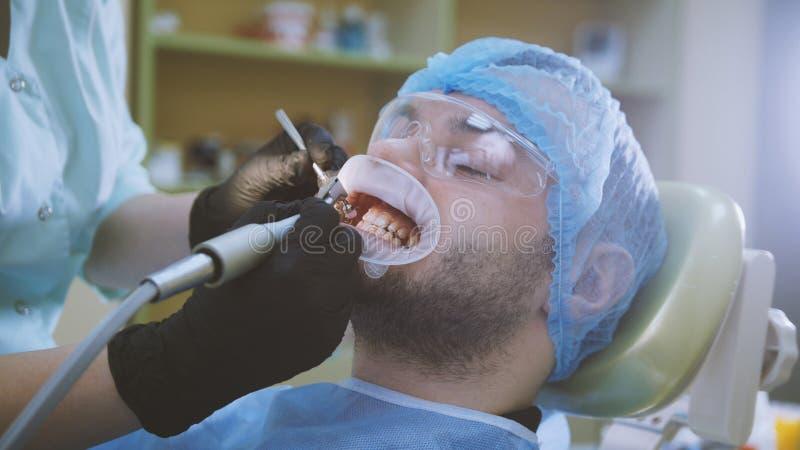 Sanità di stomatologia - paziente maschio alla sedia del ` s del dentista immagini stock