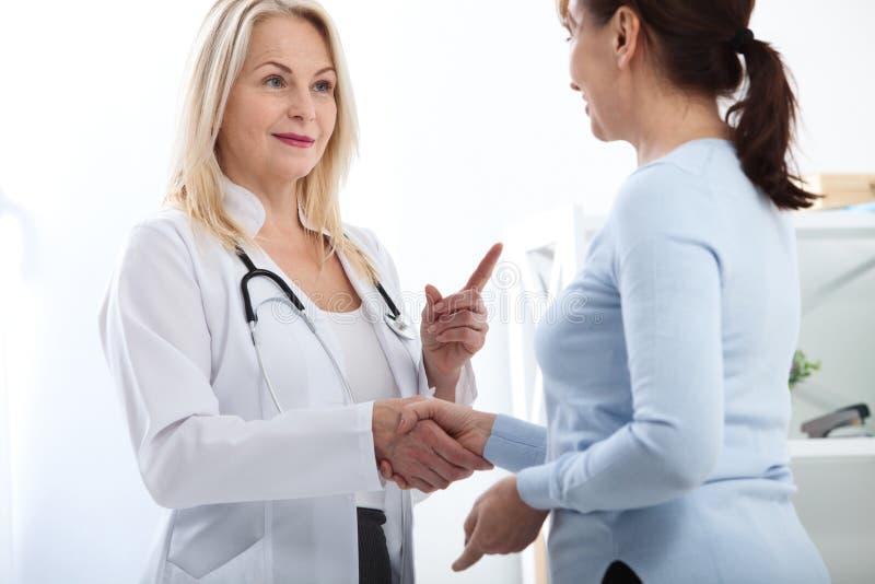 Sanità e concetto medico - medico con il paziente in ospedale Stretta di mano immagine stock