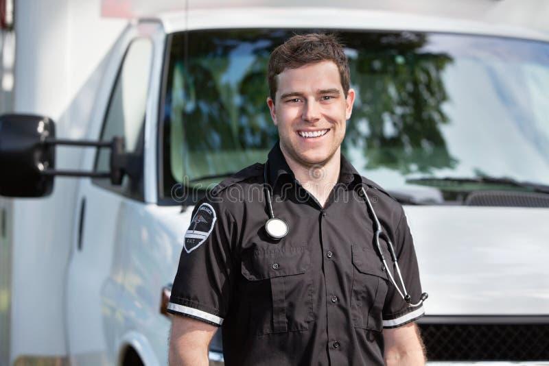 Sanitäter-Mann, der nahen Krankenwagen steht lizenzfreie stockbilder