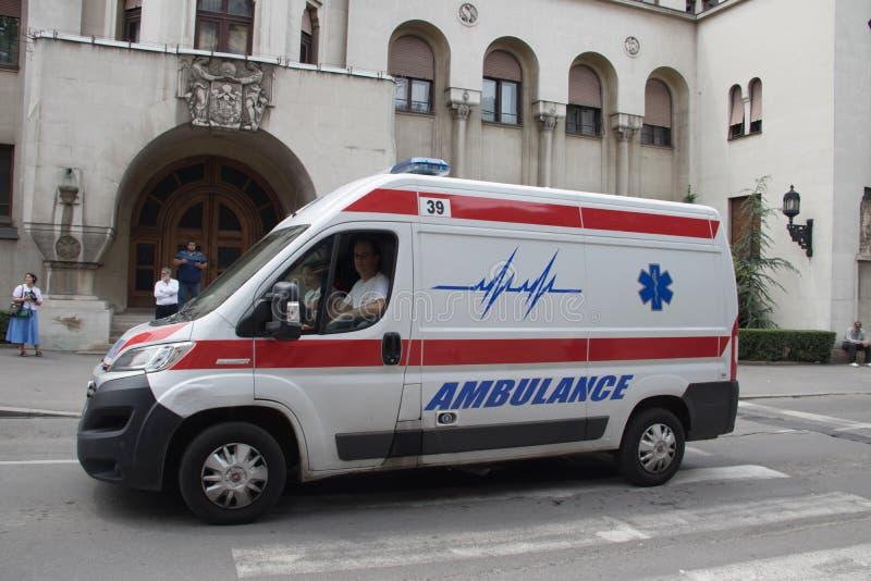 Sanitätswagen auf der Straße, mit Polizei im Hintergrund, allgemeines Ereignis sichernd lizenzfreies stockfoto