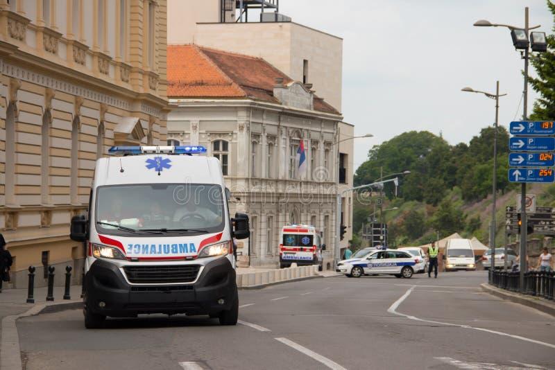 Sanitätswagen auf der Straße, mit Polizei im Hintergrund, allgemeines Ereignis sichernd lizenzfreies stockbild