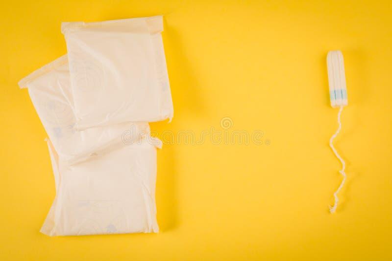 Sanitaire stootkussens en tampon op een gele achtergrond Hygiëneproduct stock afbeeldingen
