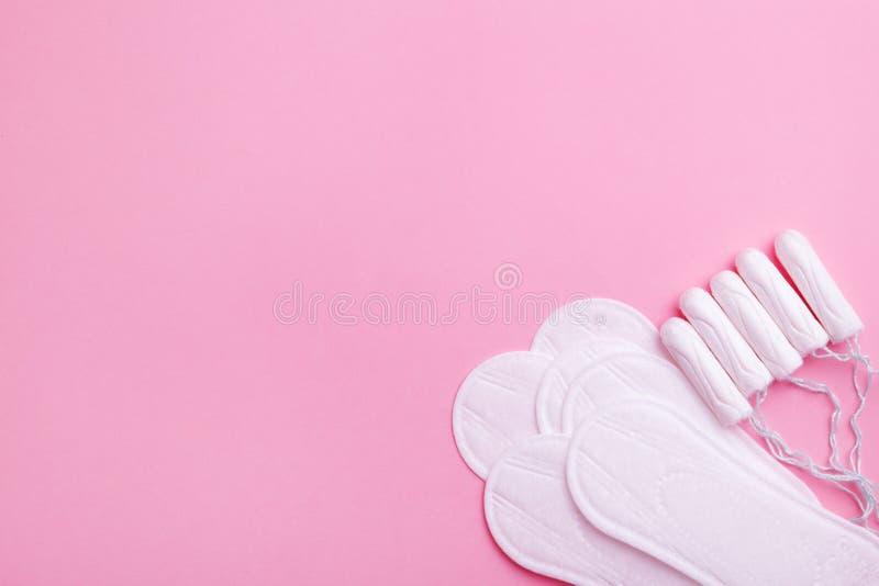 Sanitaire stootkussens en tampons op roze achtergrond, exemplaarruimte stock afbeelding