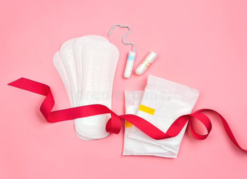 Sanitary and daily napkins, tampons with red ribbon on pink background. Concept of critical days, menstruation stock photography
