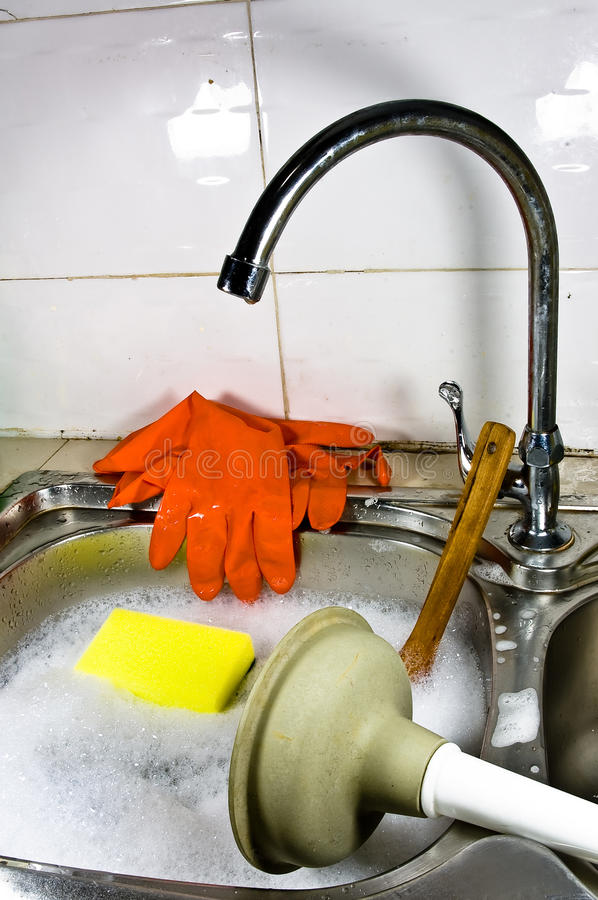 Sanitary problem still life. Sanitary problem still life with dirty sink full of water and soap foam, orange gloves, yellow sponge, shiny metal water tap royalty free stock images