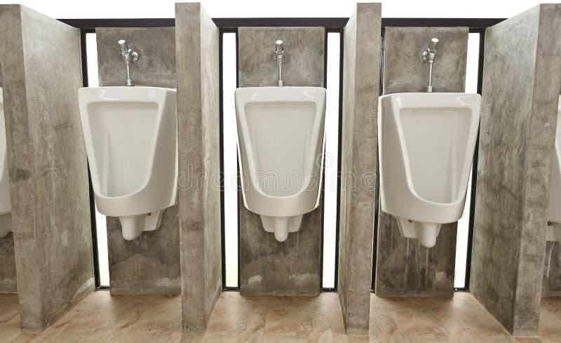 Sanitary ware in men's restroom. White ceramic sanitary ware in restroom royalty free stock image