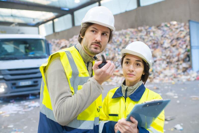 Sanitetsarbetare som arbetar med återvinningsanläggningar royaltyfri foto