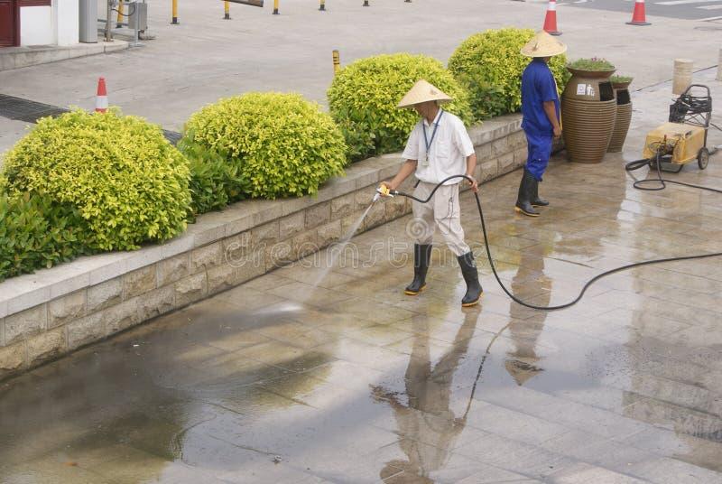 Sanitetsväsenarbetare, i att göra ren golvet royaltyfri bild