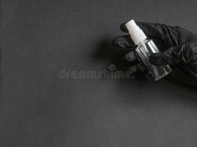 Sanitizer in een fles met spray voor de behandeling van handen en diverse oppervlakken tijdens een epidemie in een hand in een zw stock foto's