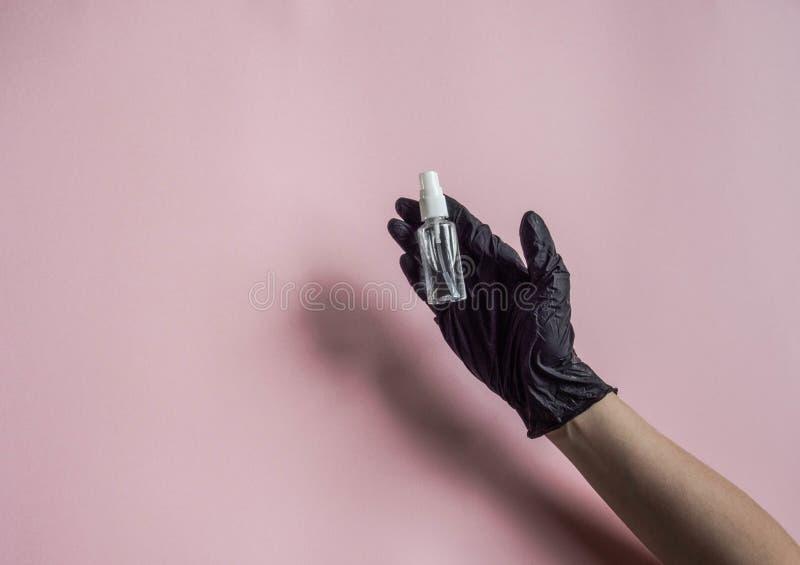 Sanitizer in een fles met spray voor de behandeling van handen en diverse oppervlakken tijdens een epidemie in een hand in een zw royalty-vrije stock foto's