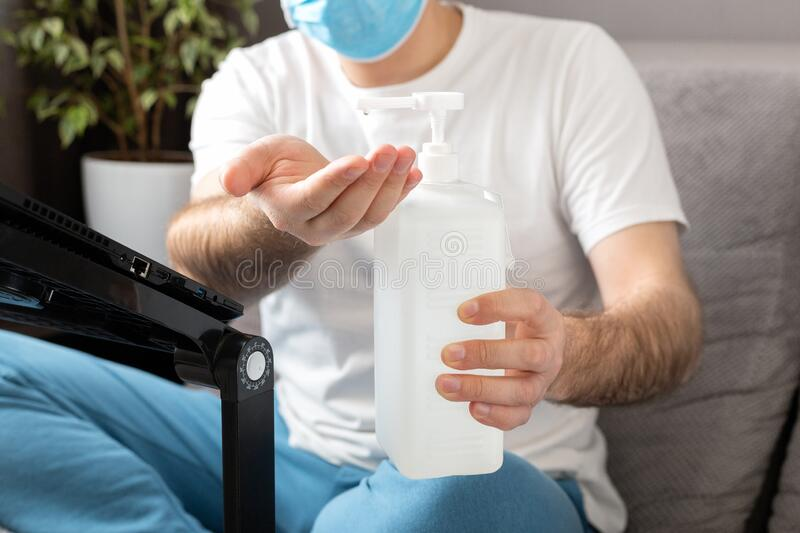 Sanitizer gel for cleaning hands in male hands. Coronavirus Covid 19 protection, hand hygiene. Freelancer in face surgical mask. Remote work at home quarantine stock photo
