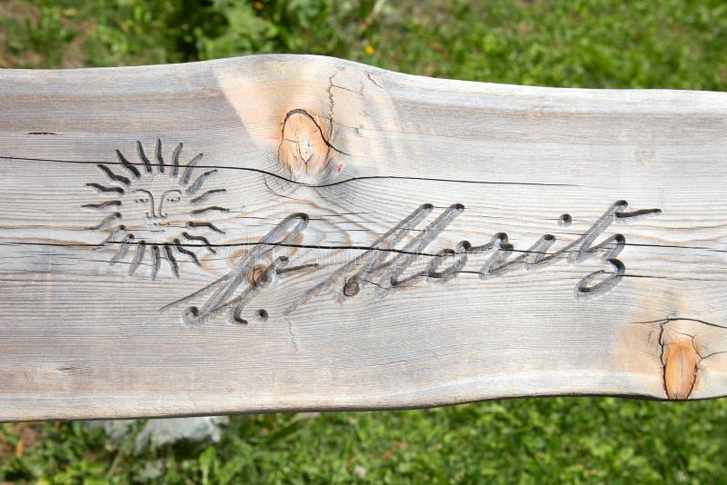 Sankt Мориц, логотип города с солнцем высекаенным в планке деревянной скамьи в солнечном летнем дне стоковое изображение