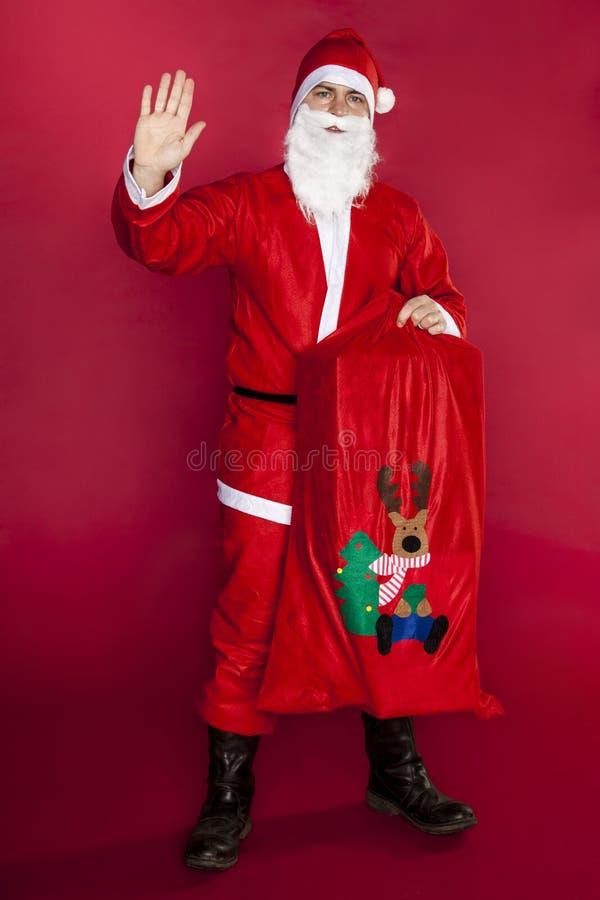 Sankt bewegte seine Hand wellenartig und hielt eine Tasche voll von den Geschenken stockbild