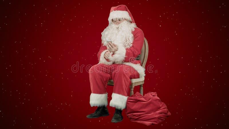 Sankt, die heraus lautes lacht, wie er an seinem Handy auf rotem Hintergrund mit Schnee spricht lizenzfreie stockfotos