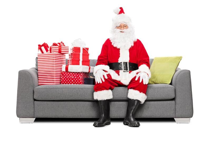 Sankt, die voll auf einer Couch von Weihnachtsgeschenken sitzt stockbilder