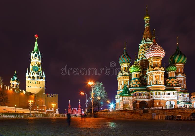 Sankt domkyrka för basilika` s på den röda fyrkanten i Moskva vid vinternatten som är upplyst vid streetlighten med Kremlväggen o royaltyfria foton