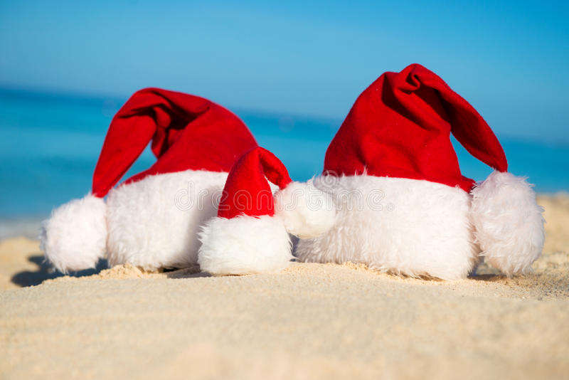Sankt-Hüte auf sandigem Strand - Konzept des neuen Jahres lizenzfreie stockbilder