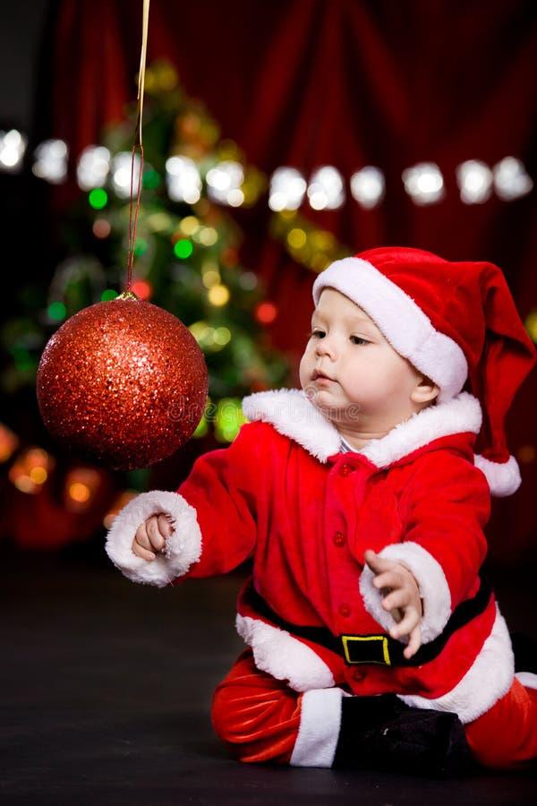 Sankt-Helfer, der mit Weihnachtskugel spielt lizenzfreies stockbild