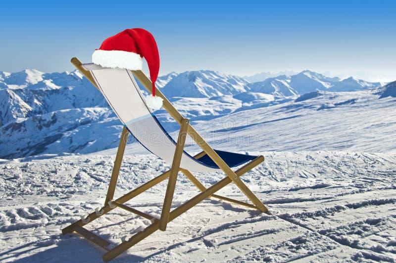 Sankt-Hut auf einem deckchair auf der Seite einer Skisteigung, schneebedeckter Berg stockbilder
