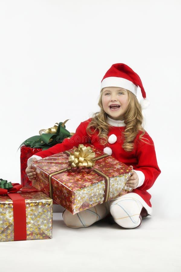 Sankt-Hut des kleinen Mädchens roter Kleidermit Geschenk auf weißem Hintergrund lizenzfreie stockbilder