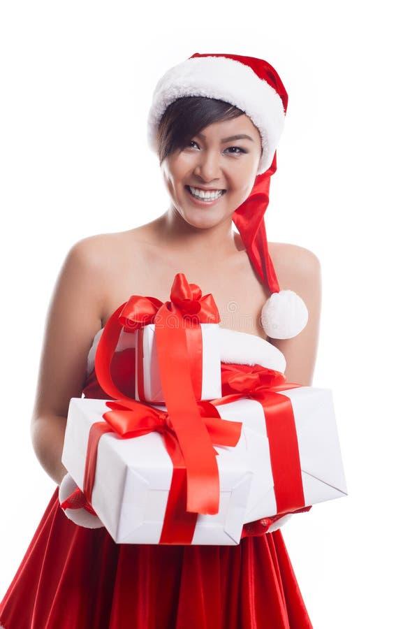Sankt-Hut Weihnachtsasiatische Frau, die das Weihnachtsgeschenklächeln hält lizenzfreies stockfoto