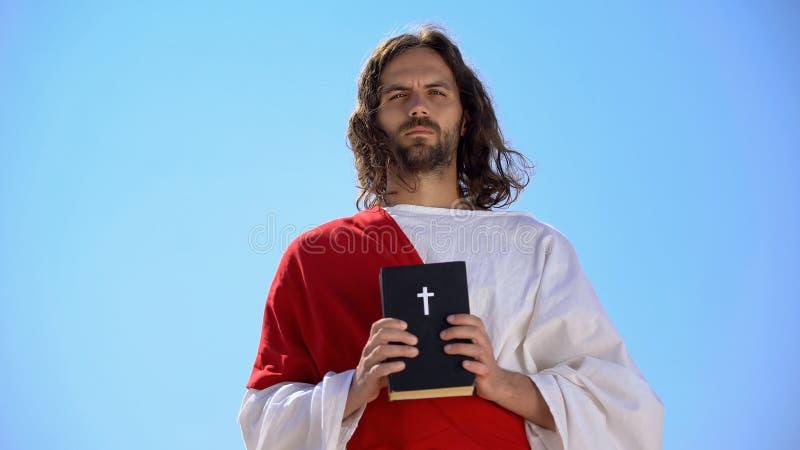 Sankt man som håller Bible mot himmel-, tros- och religionskoncept, katolicism royaltyfria foton