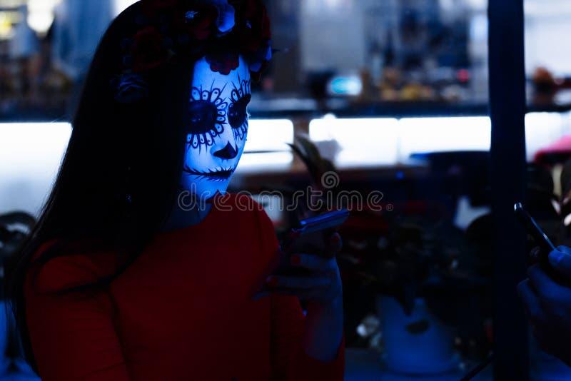 Sankt muerte Mädchen in der Dunkelheit mit Make-up Halloween, ihr Gesicht beleuchtete durch Kaltlicht vom Telefon lizenzfreies stockbild