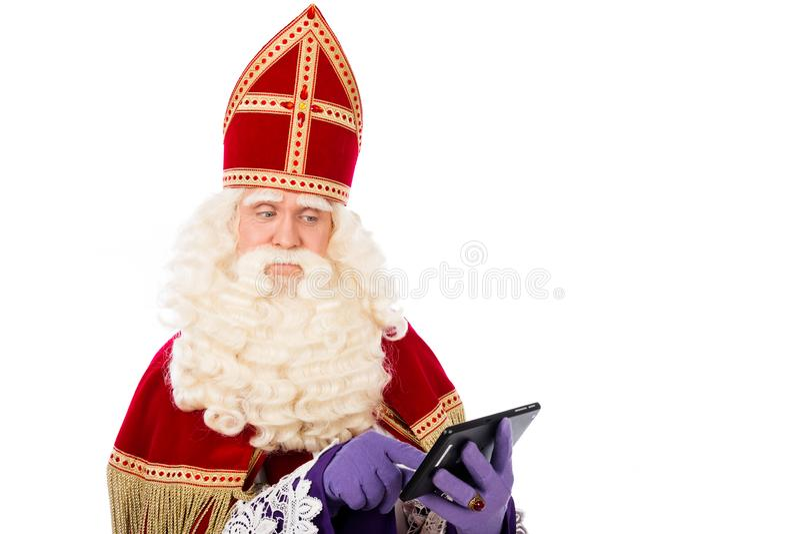 Sankt Nikolaus, der an der Tablette oder am intelligenten Telefon schaut lizenzfreie stockbilder