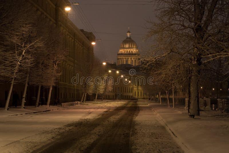 Sankt Petersburg, Rosja w ciemności zimowego ranka Katedra św. Izaaka, pusta śnieżna ulica i gołe drzewa zdjęcia stock
