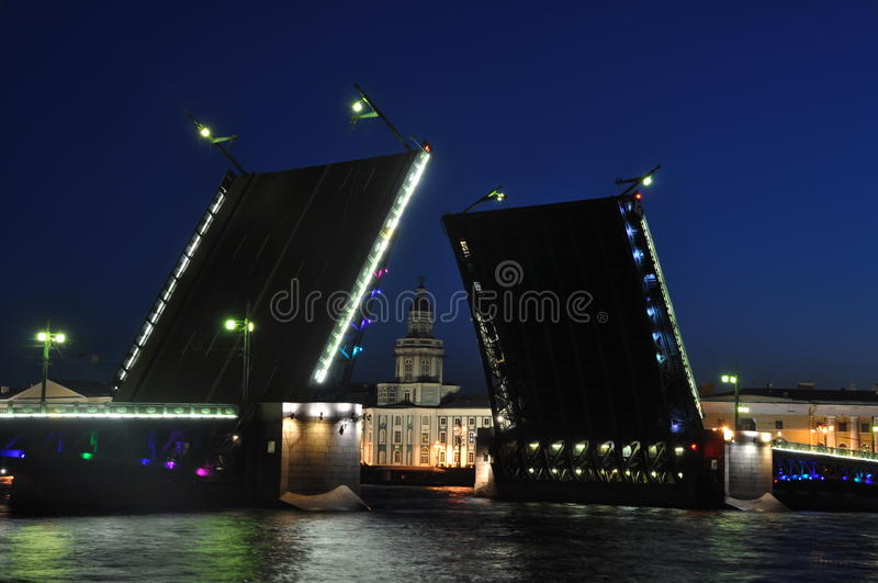 Sankt Petersburg white nights. Bridge over Neva river opening and landmark illuminated royalty free stock images