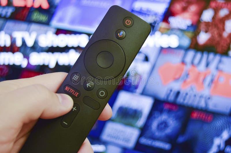 Sankt-Pietroburgo, Russia, il 30 marzo 2019: L'uomo tiene in suo telecomando della mano con il bottone di Netflix Selezioni un fi immagine stock libera da diritti