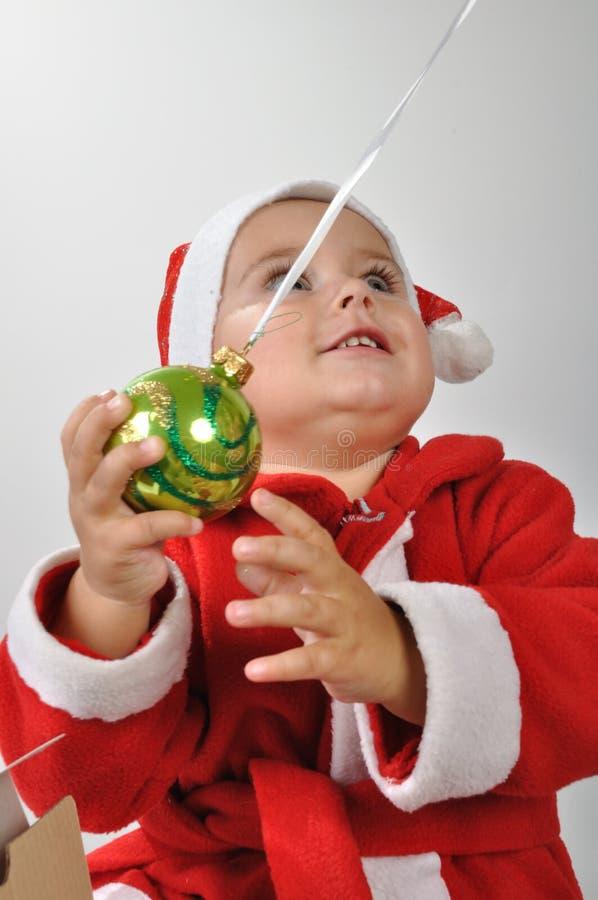 Sankt-Schätzchen, das mit einer Weihnachtskugel spielt stockbilder