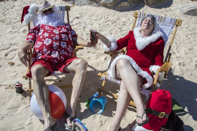 Sankt und Frau Claus, das ein tropisches Cocktail auf dem Strand teilt lizenzfreie stockbilder