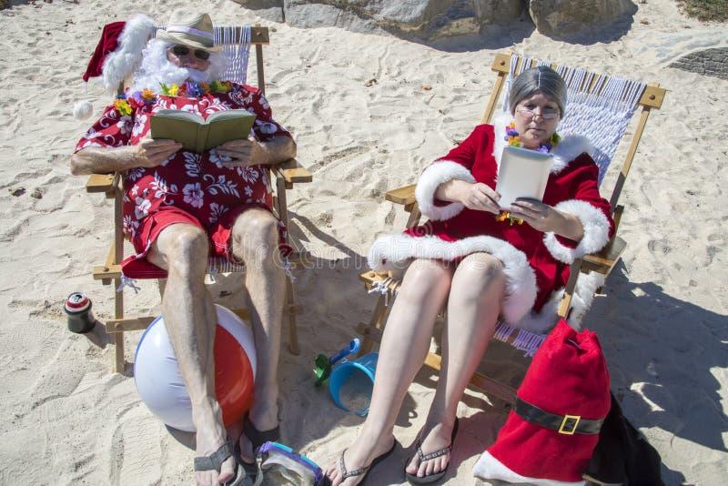 Sankt- und FrauClaus Lesebücher auf Strand lizenzfreies stockfoto