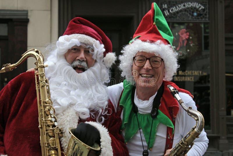 Sankt und seine Elfe mit Saxophonen am viktorianischen Spaziergang stockbilder