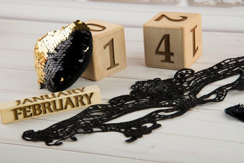 Sankt valentindagsammansättning Träkalendern, svart snör åt maskeringen och guld- paljetthjärta royaltyfri bild