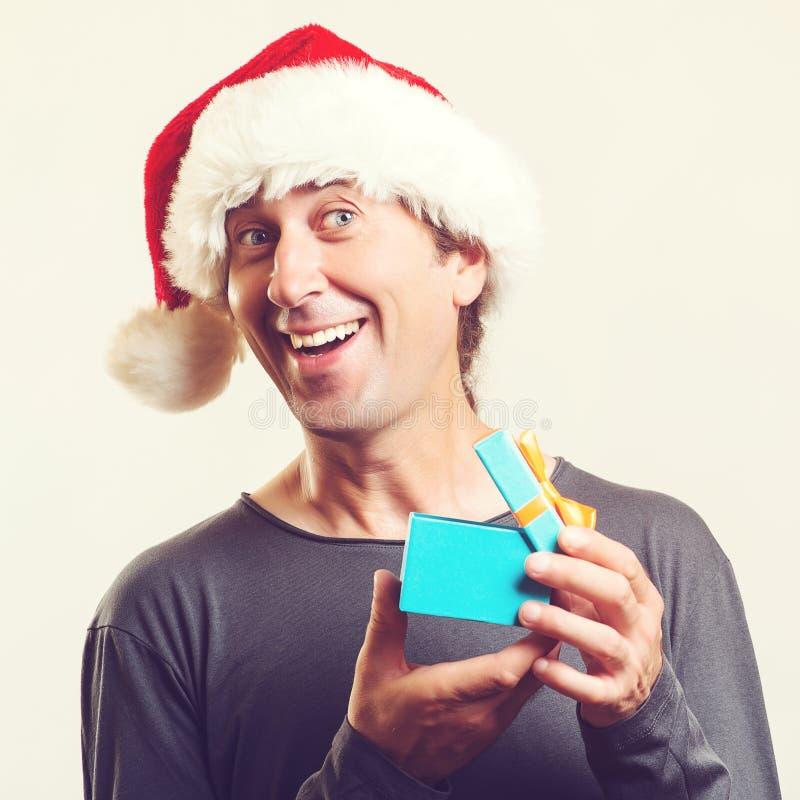 Sankt-Weihnachtsmann?ffnungs-Geschenkboxgeschenk Überraschender Mann in Sankt-Hut lokalisiert auf Weiß gl?ckliches M?dchen mit Re lizenzfreie stockbilder