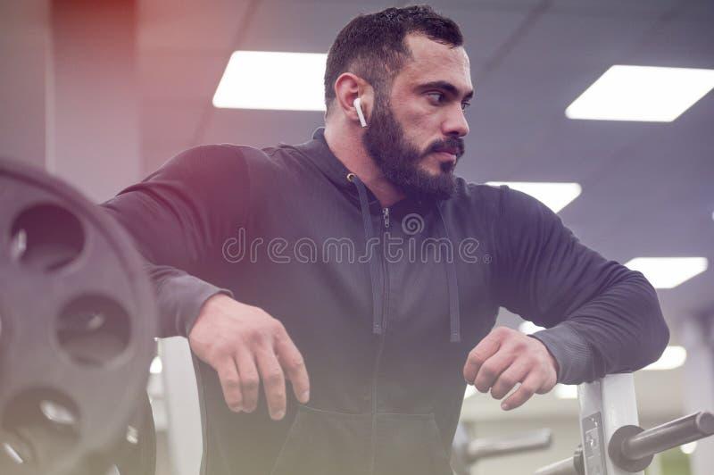 Sano joven fuerte barbudo cansado deporte hombre atento durante la pausa de relax en el gimnasio deportivo escuchar música de mot imagen de archivo libre de regalías