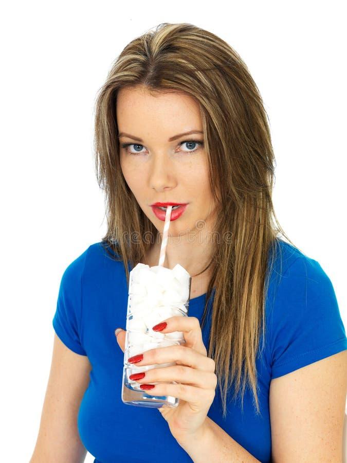 Sano malsano de la mujer joven bebiendo un vidrio de azúcar imágenes de archivo libres de regalías