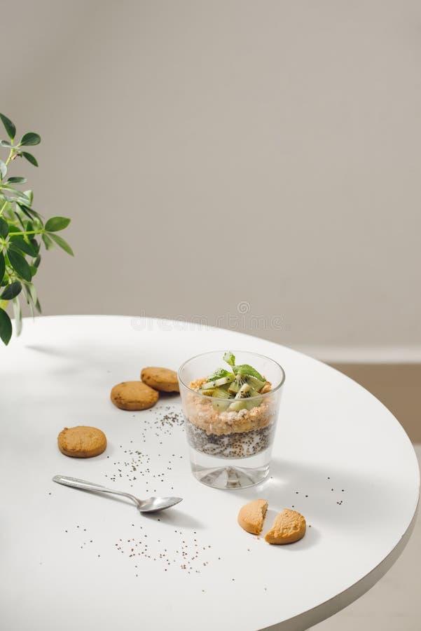 Sano preparado un desayuno nutritivo - granola con las almendras, semillas del chia, pl?tano y kiwis y bayas y un tarro con imágenes de archivo libres de regalías