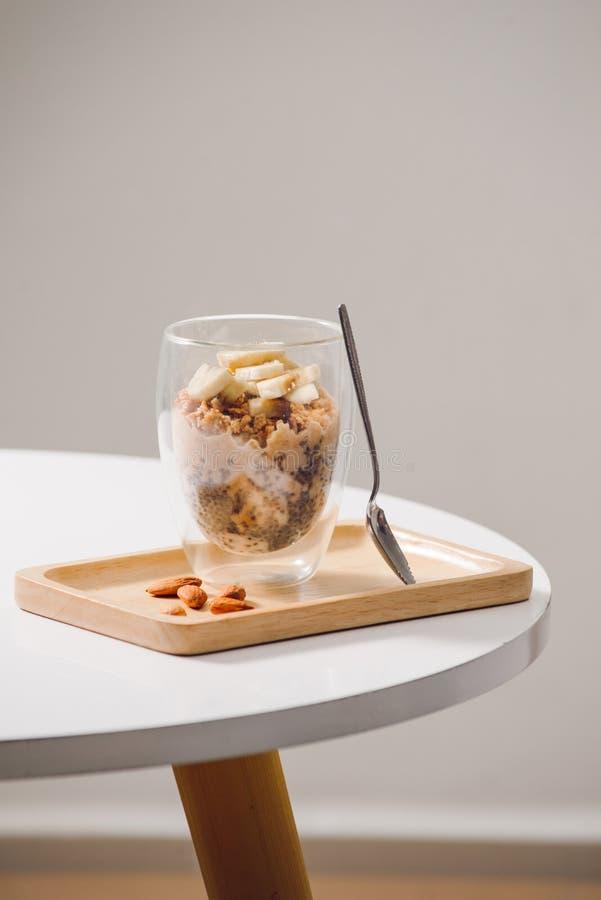 Sano preparado un desayuno nutritivo - granola con las almendras, semillas del chia, pl?tano y kiwis y bayas y un tarro con fotos de archivo