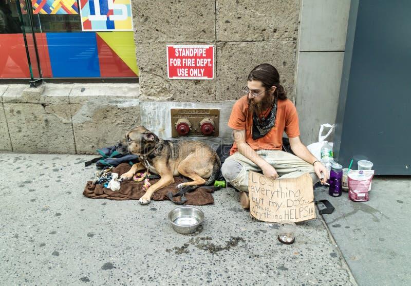 Sans-abri avec son chien dans la rue de New York images libres de droits