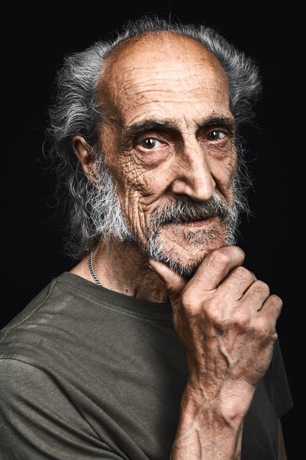 Sans abris âgé avec une main sur le menton pensant à la question photographie stock libre de droits