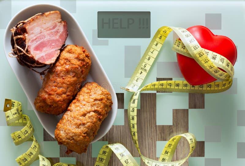 santé comprimés, coeur ainsi que la nourriture grasse comme concept de la nutrition de poids excessif et pauvre ou incitation à u photos libres de droits