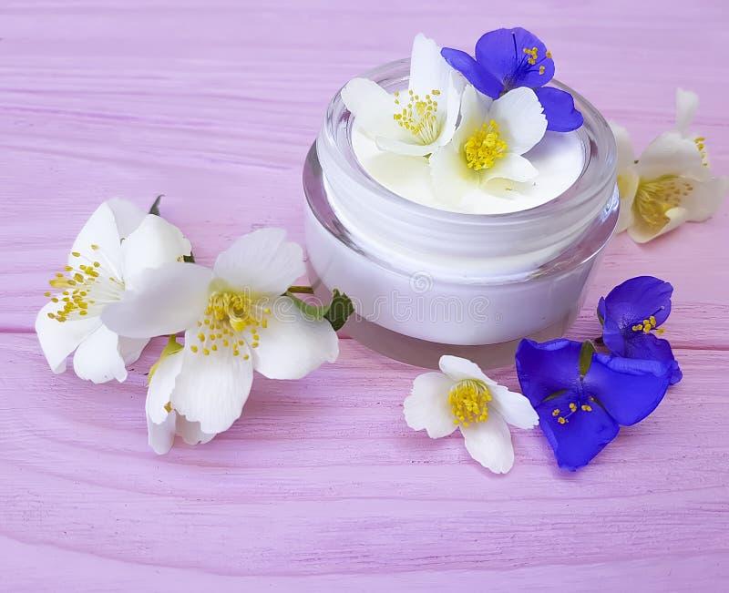 Santé cosmétique crème de fleur de jasmin de beauté de protection de crème hydratante sur un fond en bois rose photo stock
